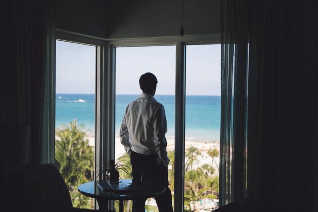novio asomado a la ventana del hotel. Carolina & Álvaro. Foto de: @fandi_es